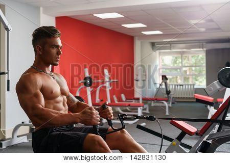 At gym. Handsome shirtless guy exercising on simulator