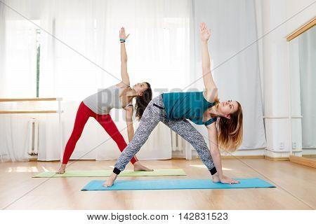 Portrait of two beautiful girls showing ashtanga vinyasa triangle yoga pose