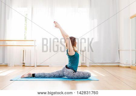Portrait full length of beautiful caucasian woman practicing eka pada rajakapotasana indoor