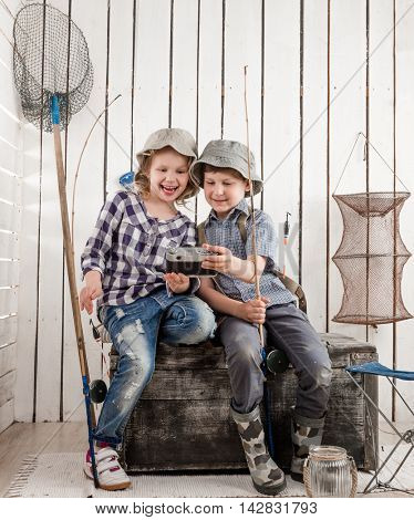 two little smiling children making selfie sitting on old big chest