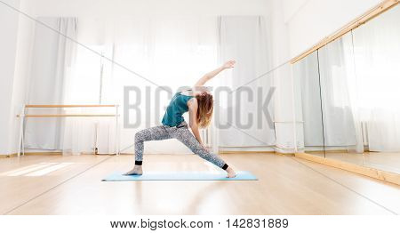 Young beautiful woman doing yoga in bright spacious studio, variation of high lunge exercise