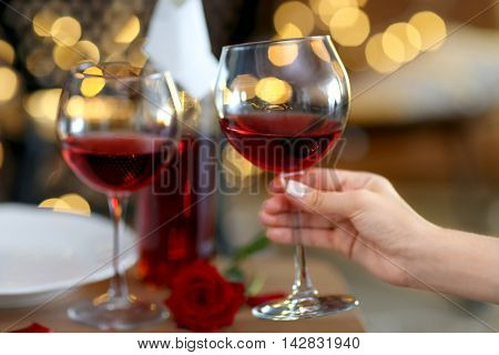 Female hand with glass of wine on blurred background