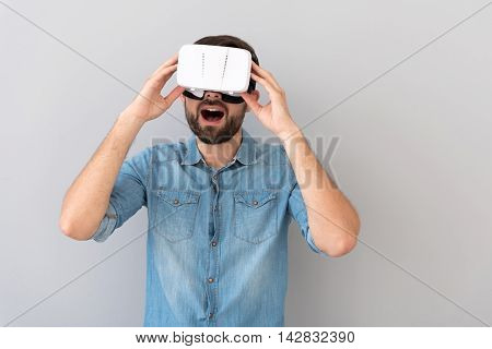 Amazing world . Overjoyed delighted man smiling and using virtual reality device while standing isolated on grey background