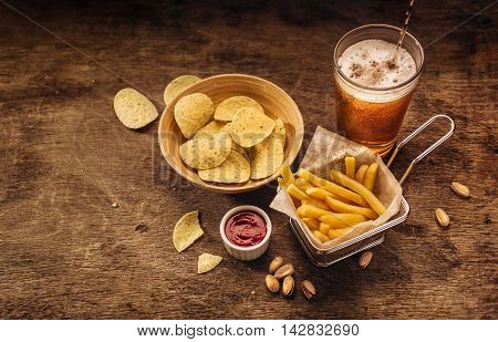 French fries, potato chips and beer on wood background