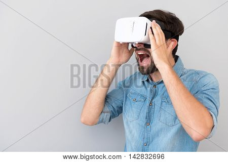 Great effect. Overjoyed delighted bearded man opening his mouth and expressing emotions while using virtual reality device