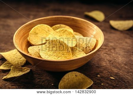 Crispy potato chips in bowl on wooden background. Closeup. Food background