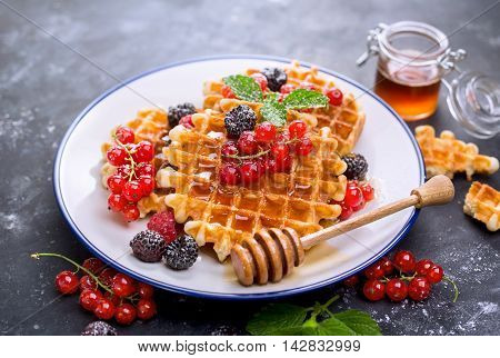 Waffles with fresh berries and honey. Breakfast with Belgian waffles