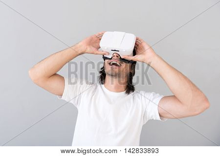 Look further. Cheerful delighted man looking up and using virtual reality glasses while standing isolated on grey background