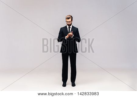 Thinking about solution. Full length studio shot of handsome young man in full suit keeping hands clasped and looking at camera