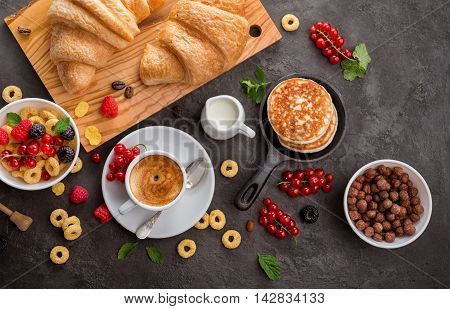 Breakfast cereals, french croissants, fresh berries and cup of coffee. Healthy food concept