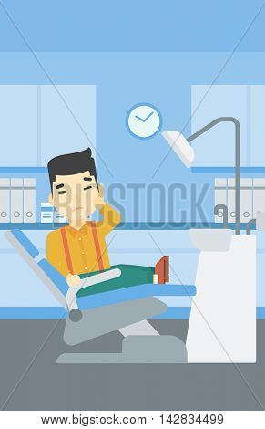 An asian young patient sitting in dental chair at dentist office. Sad man suffering from tooth pain. Man having a toothache. Vector flat design illustration. Vertical layout.