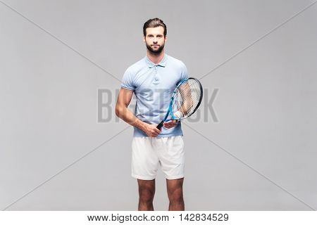Ready to play. Handsome young man in sports clothing carrying tennis racket and looking at camera