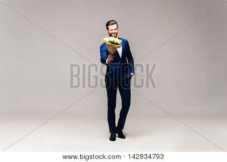 This is for you! Full length studio shot of handsome young smiling man in full suit and bow tie holding flowers and looking at them with smile