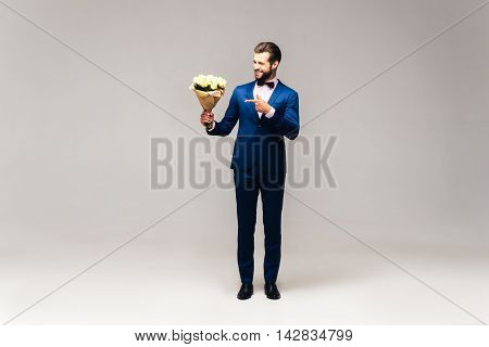 For someone special. Full length studio shot of handsome young smiling man in full suit and bow tie holding flowers and looking at them with smile
