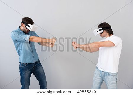 Thrilling activity. Pleasant delighted men using virtual reality glasses and being involved in game while having fun together