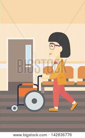 An asian young woman pushing empty wheelchair on the background of hospital corridor. Vector flat design illustration. Vertical layout.