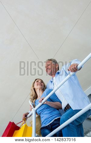 Happy couple with shopping bags by railing at home