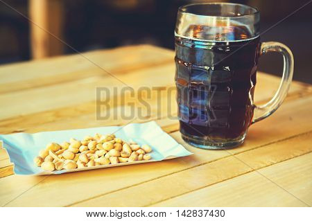 A Glass Of Cold Fresh Of Dark Beer And Salty Peanut On The Wooden Bar Counter In Pub With Free Space
