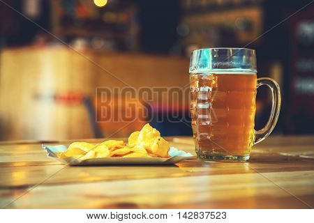 A Fresh Glass Of Cold Light Beer And Potato Chips On The Wooden Bar Counter In Pub With Free Space F