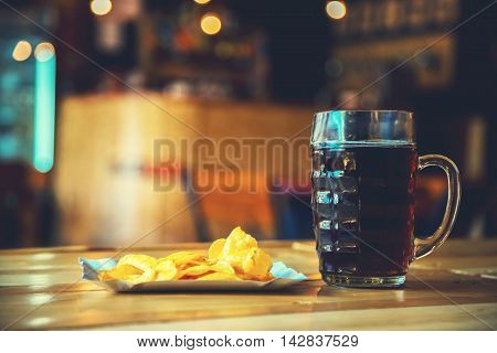 A Fresh Glass Of Cold Dark Beer And Potato Chips On The Wooden Bar Counter In Pub With Free Space Fo