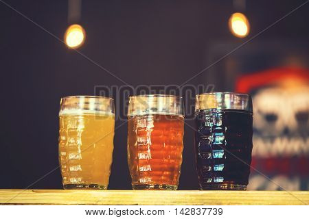 Beautiful Background Of The Oktoberfest. Glasses Of Cold Fresh White, Light And Dark Beer On The Woo