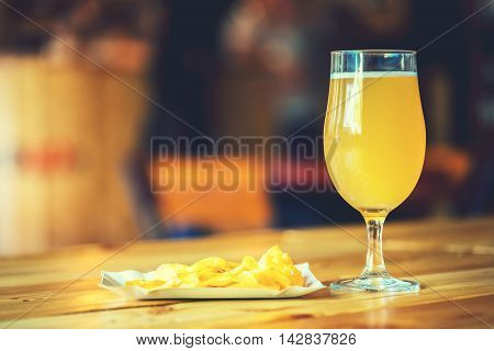 A Fresh Glass Of Cold White Unfiltered Beer And Potato Chips On The Wooden Bar Counter In Pub With F