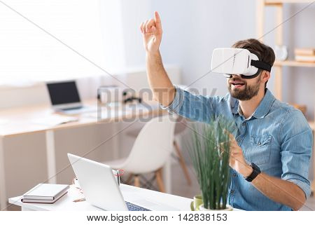 Hey. Pleasant emotional man holding his hand up and using virtual reality glasses while sitting at the table
