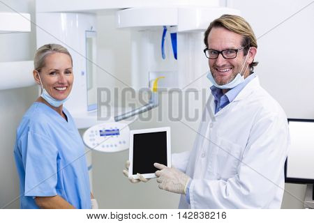 Portrait of dentist and dental assistant working on digital tablet in dental clinic