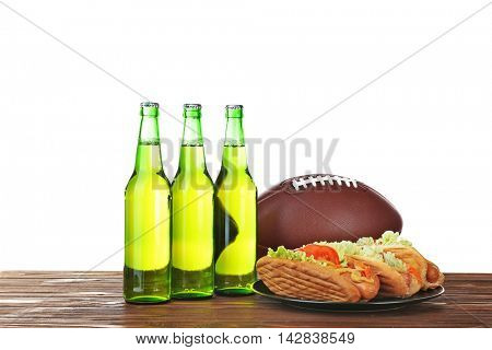 Beer bottles, ball and snack on wooden table with white background