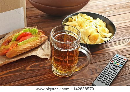 Glass of beer, snack and TV remote control on wooden background