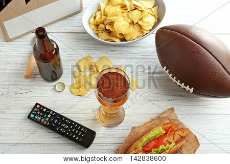 Glass of beer, bottle, snack and TV remote control on wooden background