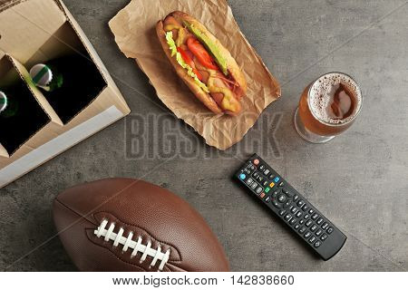 TV remote control, beer and ball on gray background