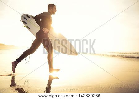 A surfer with his surfboard running to the waves