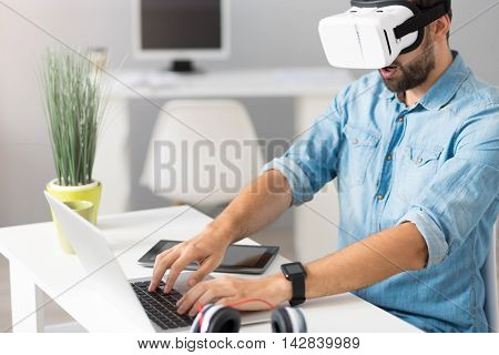 Catching moment. Involved handsome man sitting at the table and playing computer games while wearing virtual reality glasses