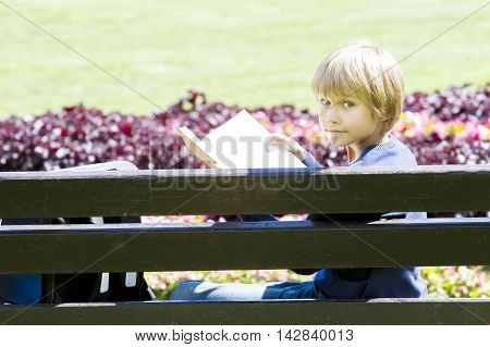 Little boy reading book on bench in the park. Child turns his head to look at the camera