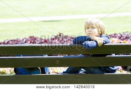 Little boy resting after the school on bench in the park after the school