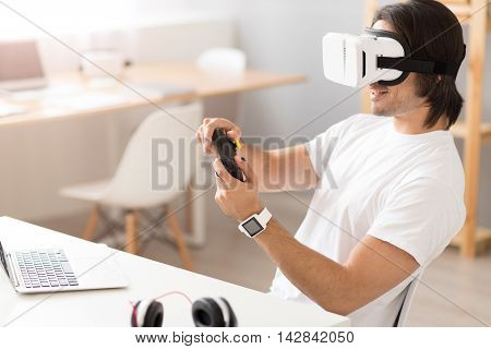 Playful mood. Cheerful young man sitting at the table and holding game console while wearing virtual reality glasses
