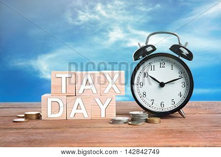 Text tax day on wooden blocks with stacked coins and alarm clock. Financial concept.