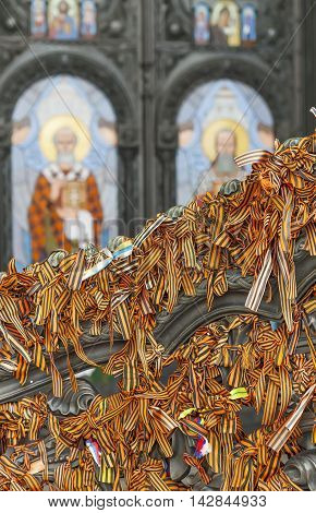 KRONSTADT, RUSSIA - AUGUST 13, 2016: Photo of St. George ribbons on the gate of the Sea (Nikolsky) Cathedral on the background of the Saints.