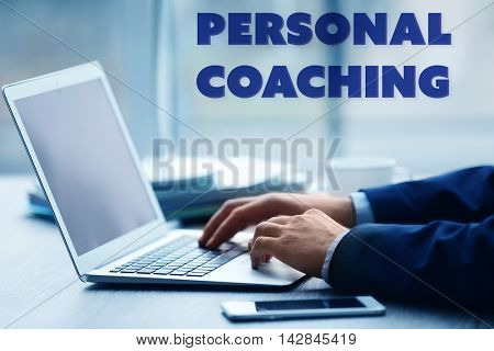 Personal coaching concept. Man's hands using laptop at the table