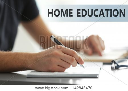 Home education concept. Student's hand writing in exercise book at the table