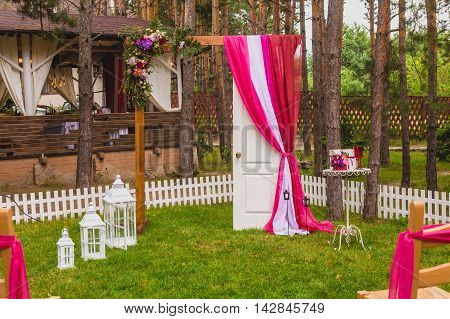 Beautiful wedding arch with door and table with box for gift, wineglasses and box for rings for ceremony in the park