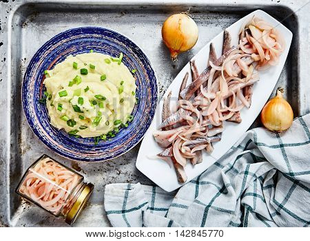 Top view shot of mashed potatoes with chopped green onion and herring fillets with pickled onions. Perfect matching of garnish on metal background, kitchen towel, fresh onions, jar of pickled onions