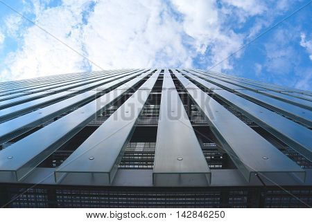 perspective view on modern facade of glass and steel with cloudy blue sky. Architectural background