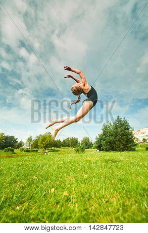 Young Beautiful Preteen Girl Doing Gymnastics Outdoors