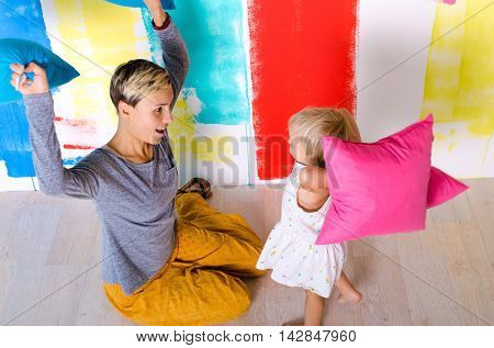 Mother and daughter have pillow fight at the kids room