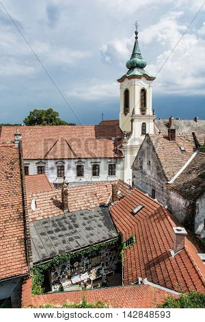 Annunciation church and red roofs of old houses Szentendre Hungary. Religious architecture. Beautiful place. Vertical composition. Place of worship.