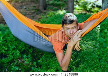 Portrait of a dreaming boy who relaxing in a hammock in the forest. Blurred background.