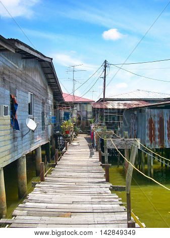 Fishing village in Brunei with wooden bridge or gangplank.