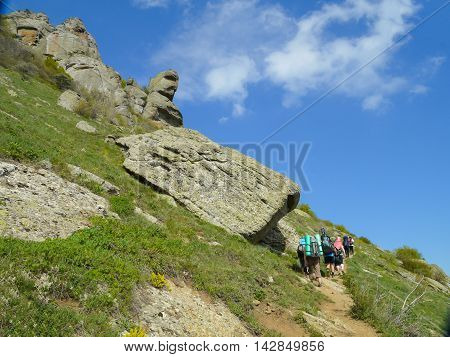 Hikers going on the hill of the mountain. Mountains in Crimea at the sunny summer day.